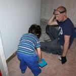 Hugo och Viktor jobbar med att ta bort klinkersplattorna i tvättstugan.